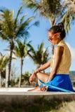La muchacha negra adolescente hermosa en falda azul se sienta con su lo del penique Fotografía de archivo