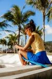 La muchacha negra adolescente hermosa en falda azul se sienta con su lo del penique Imagenes de archivo