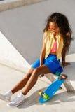 La muchacha negra adolescente hermosa en falda azul se sienta con su lo del penique Imágenes de archivo libres de regalías