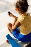 La muchacha negra adolescente hermosa en falda azul se sienta con su smartpho Foto de archivo libre de regalías