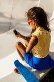 La muchacha negra adolescente hermosa en falda azul se sienta con su smartpho Fotos de archivo