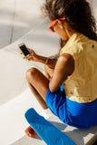 La muchacha negra adolescente hermosa en falda azul se sienta con su smartpho Imagenes de archivo
