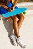 La muchacha negra adolescente hermosa en falda azul se sienta con su smartpho Fotografía de archivo
