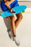 La muchacha negra adolescente hermosa en falda azul se sienta con su smartpho Imagen de archivo