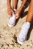 La muchacha negra adolescente hermosa en las zapatillas de deporte blancas en la arena de sea Fotos de archivo