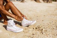 La muchacha negra adolescente hermosa en las zapatillas de deporte blancas en la arena de sea Fotografía de archivo