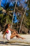 La muchacha negra adolescente hermosa se sienta en la palmera en la playa Imagen de archivo libre de regalías