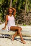 La muchacha negra adolescente hermosa se sienta en la palmera en la playa Fotografía de archivo