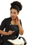 La muchacha negra agradable con un cuaderno y la pluma Fotos de archivo libres de regalías