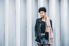 La muchacha negra con photocamera del vintage cerca modeló la pared Imagen de archivo libre de regalías