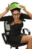 La muchacha negra en silla de la oficina en pánico cubre la cabeza con un noteb Fotografía de archivo libre de regalías