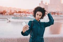 La muchacha negra está haciendo el selfie en smartphone cerca del río Foto de archivo
