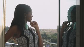 La muchacha negra joven en un vestido elegante se está colocando en el balcón y está admirando la visión metrajes