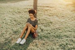 La muchacha negra se está sentando en la hierba con el smartphone Imágenes de archivo libres de regalías