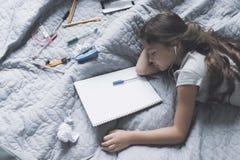 La muchacha negro-cabelluda se cayó dormido en una cama gris que escuchaba la música a través de los auriculares blancos Imagen de archivo libre de regalías