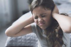 La muchacha negro-cabelluda se sienta al lado de la cama que frunce el ceño y que cubre sus oídos con sus manos Imagen de archivo