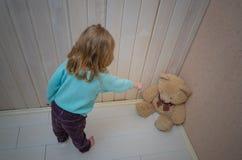 La muchacha, niño castiga, pone en la esquina del oso del juguete Imagenes de archivo