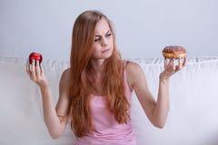 La muchacha no puede comer el buñuelo Imagenes de archivo