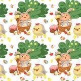 La muchacha o el muchacho inconsútil del modelo que caza el huevo de chocolate decorativo, bebé feliz se sienta en una cesta, tra Fotos de archivo libres de regalías