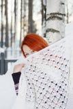 La muchacha oculta la cara detrás del mantón cerca de abedul en el invierno Foto de archivo libre de regalías