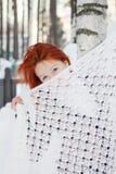 La muchacha oculta su cara detrás del mantón cerca de abedul en el invierno Imagen de archivo libre de regalías