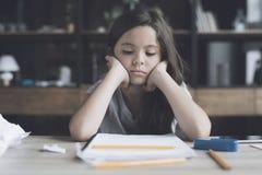 La muchacha oscuro-cabelluda apoyó su cabeza en sus manos y mira triste su cuaderno Imagen de archivo