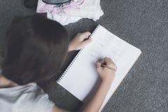 la muchacha Oscuro-cabelluda miente en el piso y dibuja un lápiz en el cuaderno blanco con un plan del lápiz Imagenes de archivo
