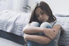 La muchacha oscuro-cabelluda se sienta en el piso con sus brazos alrededor de sus piernas y mira tristemente a un lado Fotografía de archivo libre de regalías