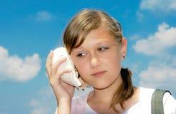 La muchacha oye el sonido del mar en el fregadero fotografía de archivo libre de regalías