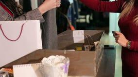 La muchacha paga con una tarjeta de crédito en una tienda de ropa, primer metrajes