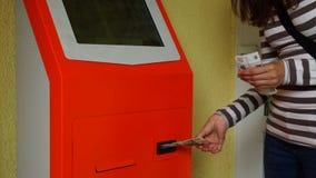 La muchacha paga el dinero a través de un cajero automático almacen de metraje de vídeo