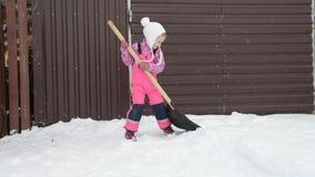 La muchacha, pala grande del bebé quita la nieve de la trayectoria en el patio trasero en el garagegirl, bebé que la pala grande  metrajes