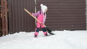 La muchacha, pala grande del bebé quita nieve de la trayectoria en el patio trasero en el garaje metrajes