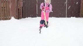 La muchacha, pala grande del bebé quita nieve de la trayectoria en el patio trasero en el garaje almacen de metraje de vídeo
