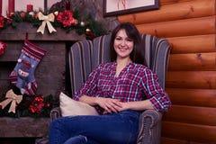 La muchacha pasa el tiempo agradable que sienta en una butaca cerca el adornamiento Imagen de archivo libre de regalías