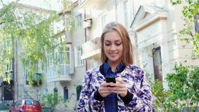 La muchacha pasa a través de la ciudad, mecanografiando en el smartphone El sol ilumina su hermoso almacen de metraje de vídeo