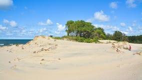 La muchacha pasa a través de las dunas de arena a la playa Fotos de archivo