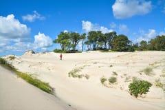 La muchacha pasa a través de las dunas de arena pintorescas Fotos de archivo