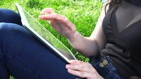 La muchacha pechugona juega en una tableta electrónica que lleva sus fingeres en el sensor almacen de video