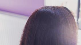 La muchacha peinó el pelo oscuro y el corte largos hermosos con las tijeras almacen de metraje de vídeo