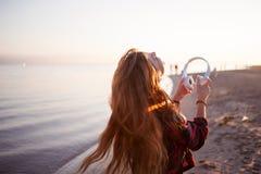La muchacha pelirroja atractiva feliz está disfrutando de música en paseo La mujer joven hermosa en camisa utiliza los auriculare Imagen de archivo