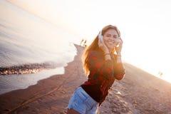 La muchacha pelirroja atractiva feliz está disfrutando de música preferida en paseo La mujer joven hermosa en camisa utiliza los  Foto de archivo