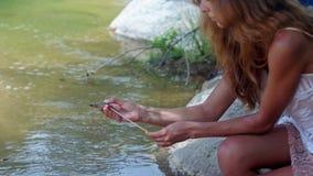 La muchacha pelirroja de la vista lateral Prinks el camarón con el palillo en la orilla del río almacen de video