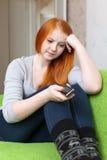 La muchacha pelirroja del adolescente espera llamada telefónica Imágenes de archivo libres de regalías