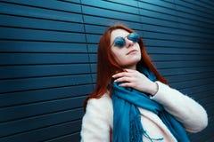 La muchacha pelirroja del inconformista en gafas de sol elegantes está presentando delante de una pared negra en la calle Fotografía de archivo