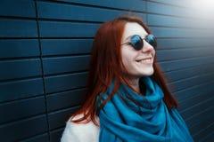 La muchacha pelirroja del inconformista en gafas de sol elegantes está presentando delante de una pared negra en la calle Fotos de archivo