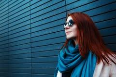 La muchacha pelirroja del inconformista en gafas de sol elegantes está presentando delante de una pared negra en la calle Foto de archivo