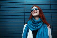 La muchacha pelirroja del inconformista en gafas de sol elegantes está presentando delante de una pared negra en la calle Imagen de archivo