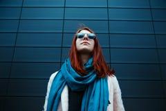 La muchacha pelirroja del inconformista en gafas de sol elegantes está presentando delante de una pared negra en la calle Imágenes de archivo libres de regalías