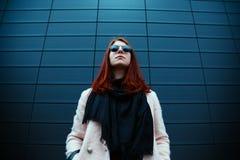 La muchacha pelirroja del inconformista en gafas de sol elegantes está presentando delante de una pared negra en la calle Fotografía de archivo libre de regalías